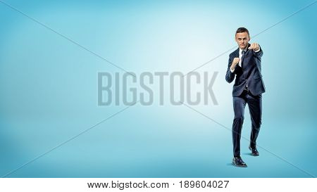 A serious businessman in front view throwing punches while standing on blue background. Fight for success. Overcome difficulties. Personal growth.