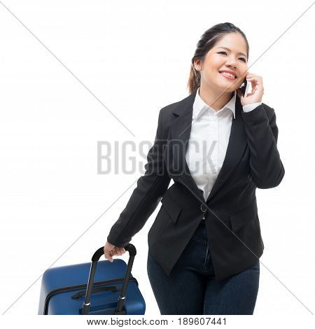 Businesswoman Talking On Mobile Phone While Carrying Luggage