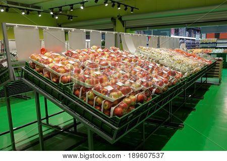 Apples in plastic packs, big supermarket store