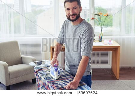 Mid shot of athletic sir ironing diligently shirt on ironing board