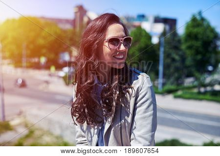 Mid shot of beautiful brunet in sunglasses enjoying view of city from building top