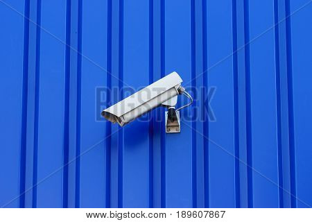 The surveillance camera on a blue background