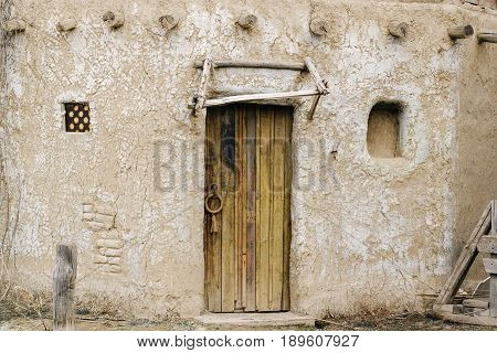 Old ancient clay wall with aged wood door with door knob