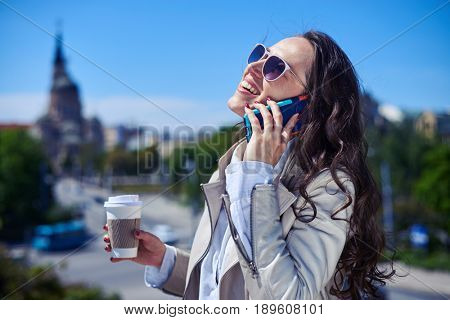 Mid shot of pretty female talking on phone while drinking coffee on top of building