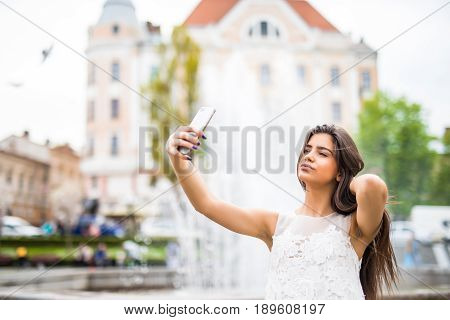 Happy Young Female Traveler Taking Selfie On Street.