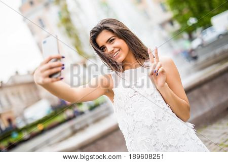 Happy Young Female Traveler Taking Selfie On Street With Victory Sign