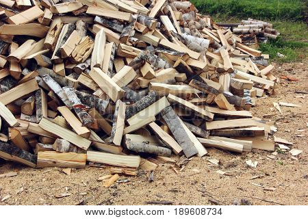 pile of logs on the grass chopped by an axe. firewood for heating furnaces.