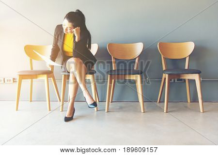 Tired of waiting. Businesswoman holding paper and looking away while sitting on chair against grey background