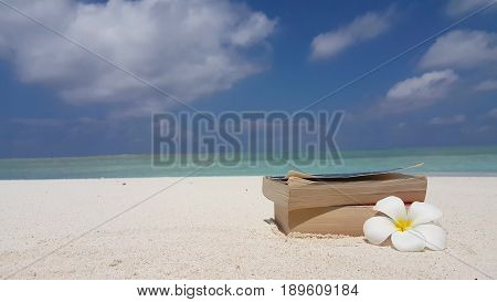 Maldives white sandy beach reading book yellow flower on sunny tropical paradise island with aqua blue sky sea water ocean 4k