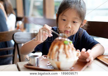 Asian Child Enjoys Eating Korean Patbingsu Or Bingsu, Shave Ice Frozen Dessert