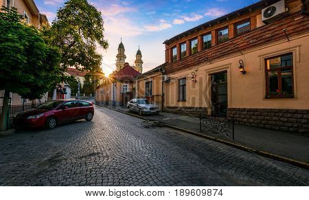peaceful sunrise in old european town. sun above the roofs on empty street to Cathedral