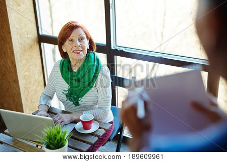 Senior woman listening to her buddy while typing