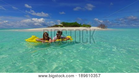 4k Maldives white sandy beach 2 people young couple man woman floating on airbed inflatable mattress swimming splashing on sunny tropical paradise island with aqua blue sky sea water ocean.