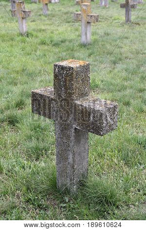 Old cross on a grave overgrown with grass in the military cemetery