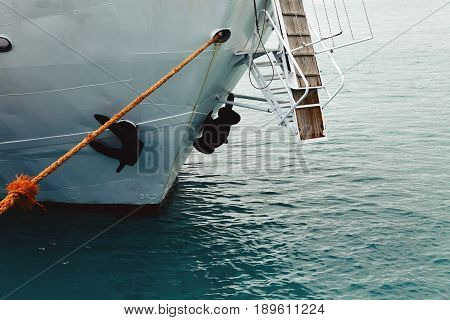 The nose of the ship is close up. Sea liner or cargo ship fixed with a rope or moored to a harbor berth