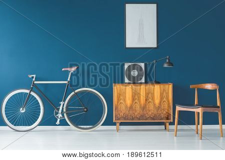 Beutiful bike and retro furniture on blue wall