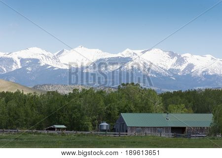 Barn in green field with fenced pasture in foreground with rugged snow capped mountains in the background.