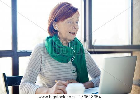 Senior woman with earphones looking at laptop display