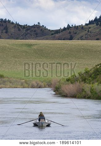 Fisherman in a boat photographed from behind on the Missouri River with foothills in the background. One fisherman is rowing the boat upstream.