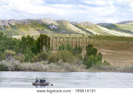 Two men fishing and a third man rowing in the Missouri River with backs to the camera. Foothills with green grasss are in the background.