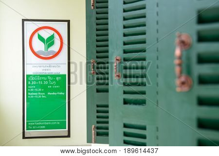 May 11 2017. Close-up detail of a sign in front of a Kasikorn Bank branch with wooden windows on the side. Vientiane Laos. Asia and finance editorial concept.