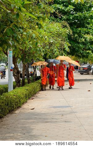 May 11 2017. Multiple novice monks holding umbrellas walk together the pavements of Vientiane Laos. Travel and people editorial concept.