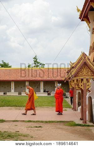 May 11 2017. A monk takes a photograph of a fellow monk at Phra That Luang Temple Vientiane Laos. Vertical orientation. Travel and religion editorial concept.