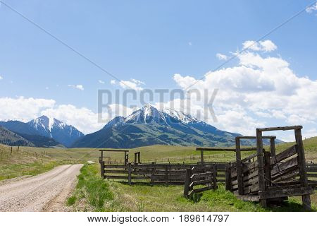 Close up of a old wooden corral in the foreground with a gravel road leading to rugged snow capped mountains in the background.