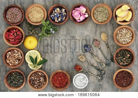 Herb tea selectionn in wooden bowls and old spoons with strainer, teas also used in natural alternative medicine.