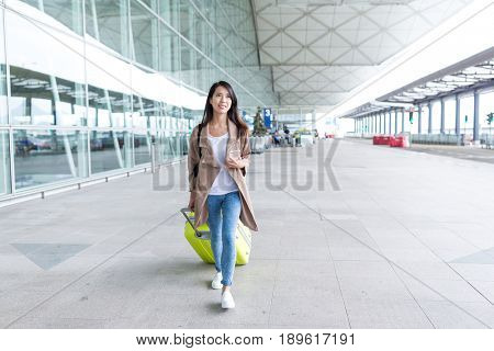 Woman walking with luggage in airport