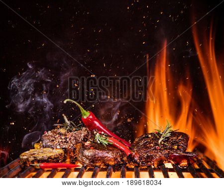 Tasty Beef steaks on the grill with fire flames