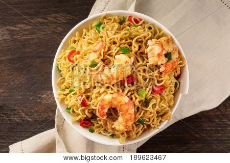 A bowl of instant Chinese noodles with green onions, red hot chilli peppers, and shrimps, shot from above on a dark rustic texture with a place for text