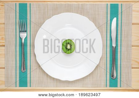 fresh kiwi on white plate spoon and fork on wooden table
