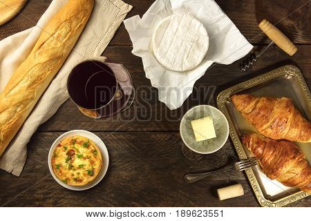 Overhead photo of assortment of French food with place for text. Baguette, red wine, quiche, camembert cheese, croissants with butter, shot from above with wine cork and corkscrew, with copy space