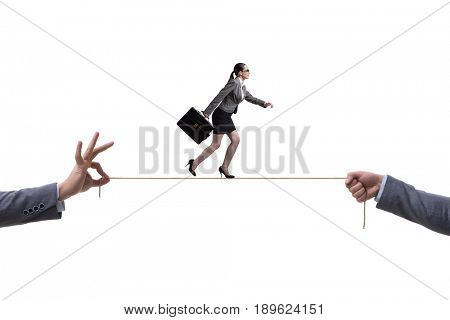 Businesswoman walking on tight rope in business concept