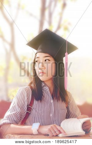 portrait beautiful asian woman with graduate cap looking up from the book thinking about future career. soft tone.