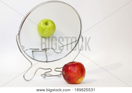 Apple reflecting in the mirror. Old and young apple