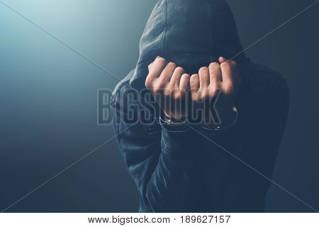 Arrested computer hacker and cyber criminal with handcuffs wearing hooded jacket hiding face