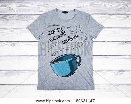 Grey shirt with coffee cup and text print. Aged wooden plank background. Every moment matters