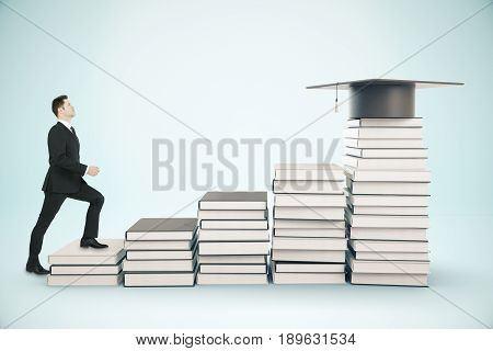 Young businessman climbing creative book ladder with graduation cap on top. Blue background. Education concept. 3D Rendering