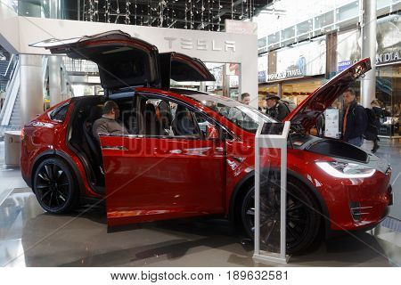 AMSTERDAM, NETHERLANDS - JANUARY 5, 2017: People at the Tesla car exposed in the airport Schiphol. First Tesla car was launched in 2008