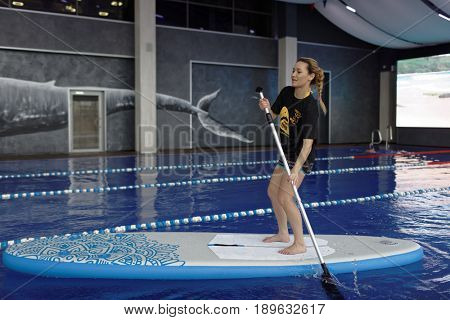ST. PETERSBURG, RUSSIA - MARCH 27, 2017: Girl demonstrate the stand up paddle board produced by Time Trial company. Founded in 2000, now the company produce a wide assortment of sport equipment
