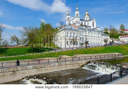 VITEBSK BELARUS - MAY 15 2017: Holy Dormition Cathedral on Assumption Mount and Holy Spirit Monastery at river Vitba. Unknown nun admires beautiful spring view