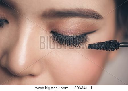 Close-up portrait of beautiful girl touching black mascara to her lashes poster