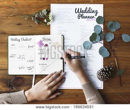 Hands Checking on Wedding Planner Notebook