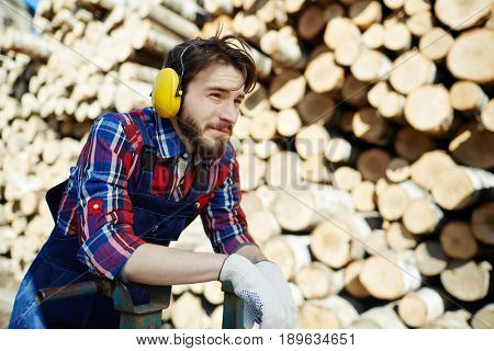 Tree worker in protective headphones pushing forklifter