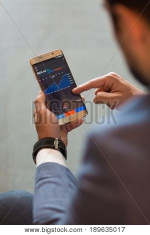 Close up of a businessman using smart phone. Focus on mobile device.