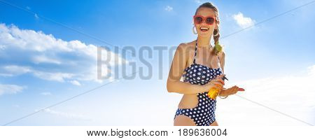 Smiling Young Woman In Swimsuit On Seashore With Spf