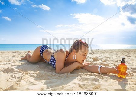 Relaxed Young Woman In Swimsuit On Seacoast With Spf