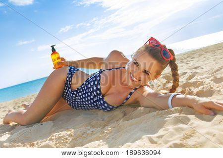 Happy Healthy Woman In Swimsuit On Beach With Suntan Lotion